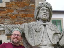 Mark Shiner next to a stone statue