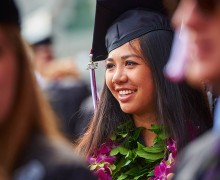 Student with flowery leis in graduation garb