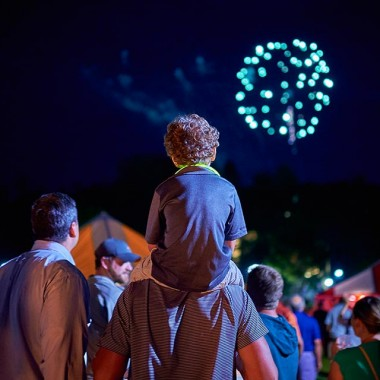 Child watches fireworks from his father's shoulders amid the reunion tents