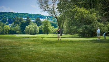 Golfer driving on Seven Oaks with Colgate's campus in the background