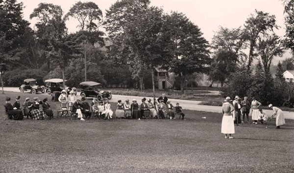 Archival photo of spectators watching others golf