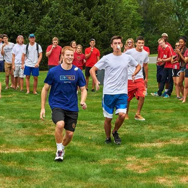 Students race while carrying an egg on a spoon in their mouths