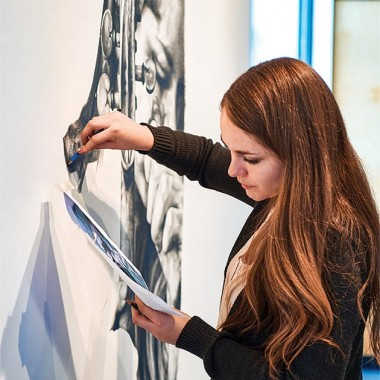 Deirdre Plaus '15 works on a portrait of herself tuning her violin.