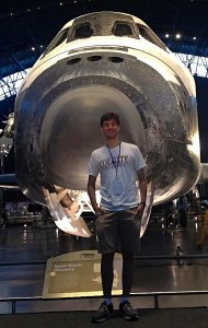 Warren Dennis '16 in front of space shuttle
