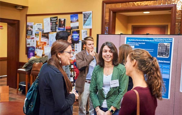 Students chat with alumni at poster presentation