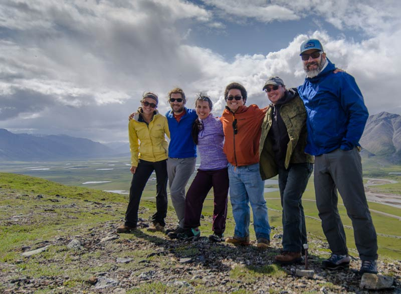 Research team in the field with mountains in the background