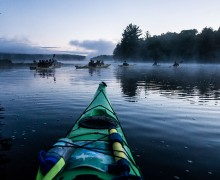 Students kayak through the morning mist on Cranberry Lake in the Adirondacks