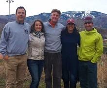 Colgate alumni in Colgate attire in front of a mountain backdrop