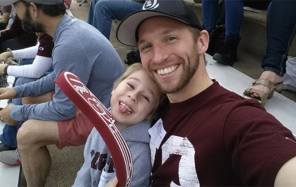 Devon Skerritt '00 and his 5-year-old son, Cullen in the stands