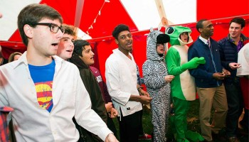 The Colgate Thirteen sing a capella in costumes at a Halloween tailgate