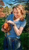 Student holding a chicken and smiling