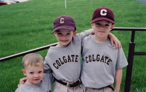 Three children in Colgate t-shirts and baseball caps on a staircase