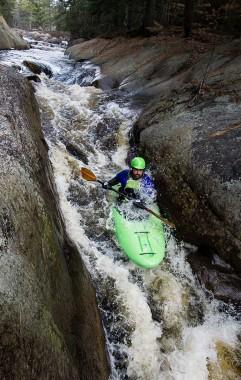 Student kayaks through rapids