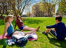 Chloe Weiss '18, MaryKathryn McCann '18, and Brendan Corrodi '18 take a study sunshine break on the residential quad.