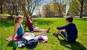 Chloe Weiss '18, MaryKathryn McCann '18, and Brendan Corrodi '18 take a study sunshine break on the residential quad.