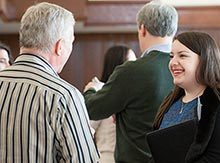 Maggie Dunne '13 speaks with an alumnus in the Hall of Presidents