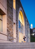 Student enters Case Library with Memorial Chapel at dusk visible in the background