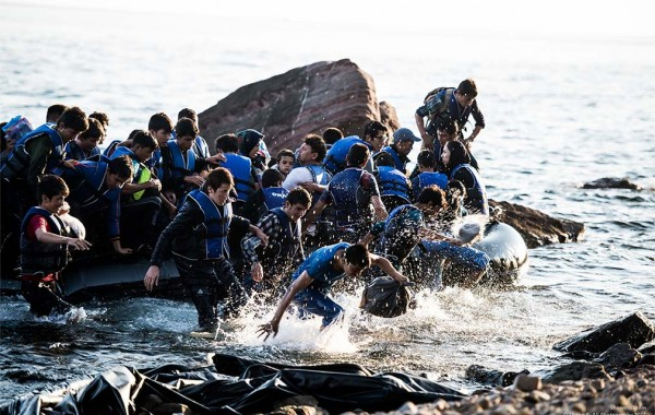 Refugees jumping into water from a precarious vessel near the beach