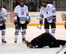 Coach Don Vaughan kissing the ice after the men's hockey team's last game in Starr Rink.