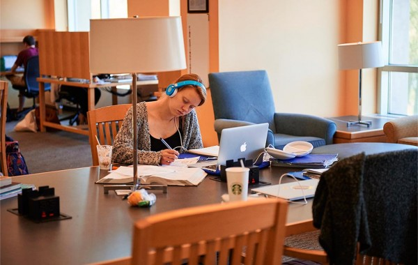 A student wears headphones while working in Case Library