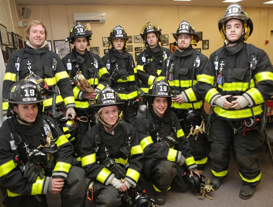 Firefighters pose for a photo in their gear at the station