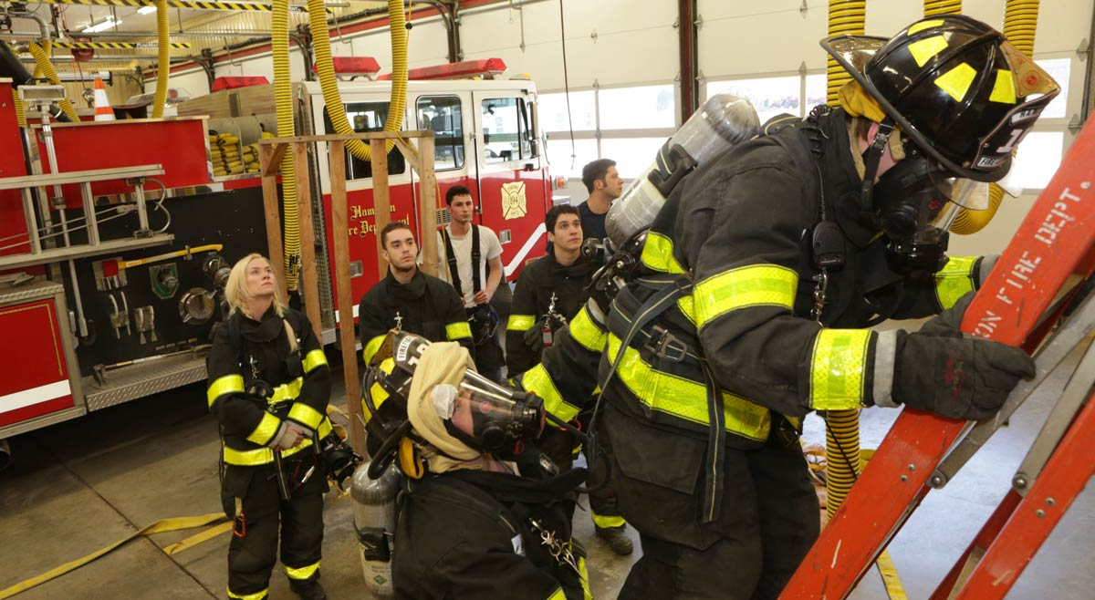 Students in gear drill on a ladder at the station