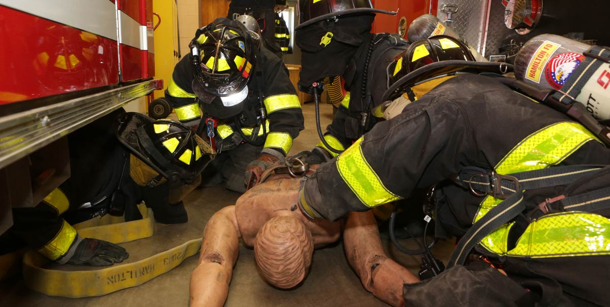 Firefighters drill on a dummy at the station