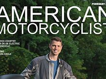 Ben Rich '99 standing by his electric motorcycle on the cover of American Motorcyclist