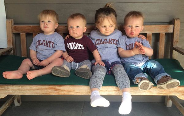 Babies sitting on bench in Colgate t-shirts.