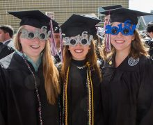 Three female graduates in caps and gowns wear 2016 sunglasses
