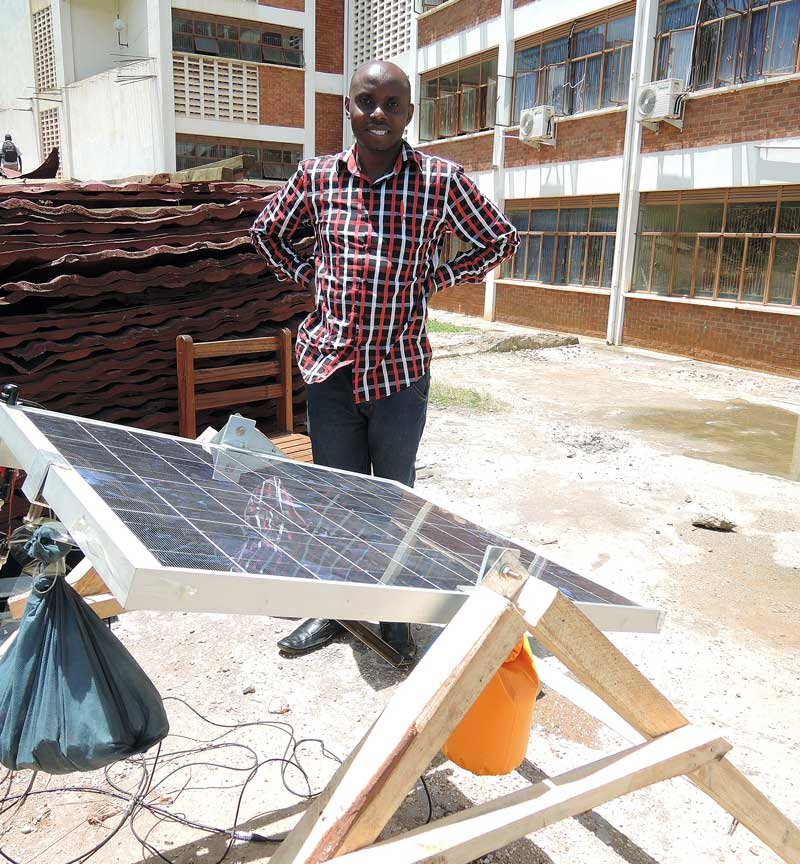 Lawrence Muzoora with a rotating solar panel