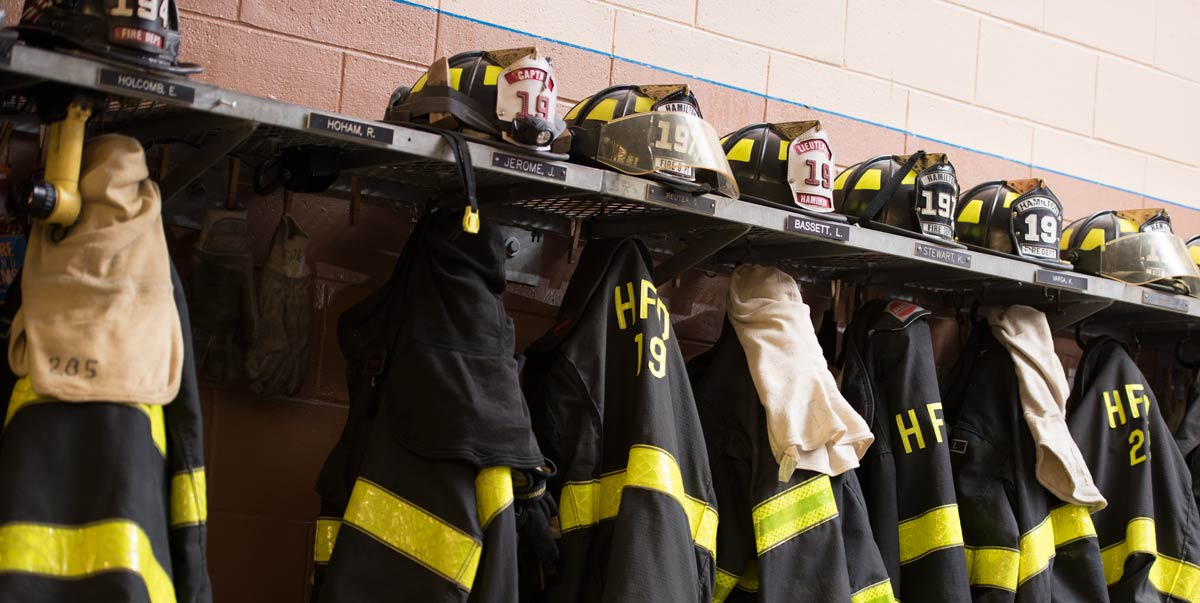 Uniforms and helmets on hooks and shelves at the station