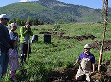 Jason Barto '89 leads a group planting trees with a mountain in the background