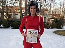 Lee McConaughy Woodruff '82 standing in the snow in red longjohns with an issue of Real Simple magazine