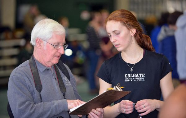 Cross country/track and field coach Arthur McKinnon consults a clipboard with an athlete