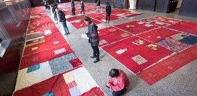 Visitors review the monument quilt in the Hall of Presidents