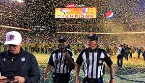 Two officials walk off the football field as confetti flies