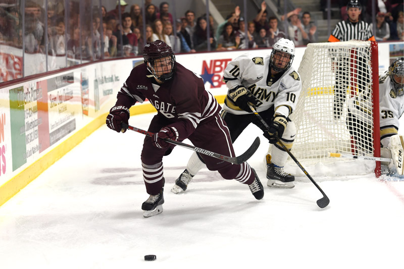 Colgate player chases the puck while a player from Army is in pursuit