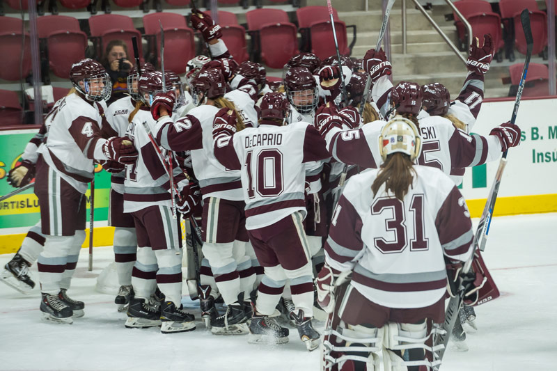 The women's hockey team celebrates on the ice
