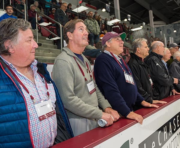 Members of the Class of 1965 stand by ice, observing the scoreboard