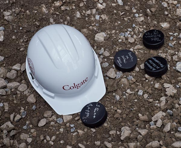 Colgate hardhat with 4 signed hockey pucks