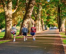 Three students in athletic attire walk along Oak Drive.