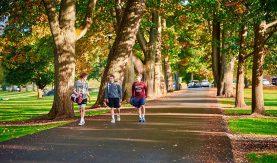 Three students in athletic attire walk along Oak Drive.