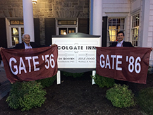 Mike '56 and Ron Costanzo '86 outside the Colgate Inn with flags for their respective class years