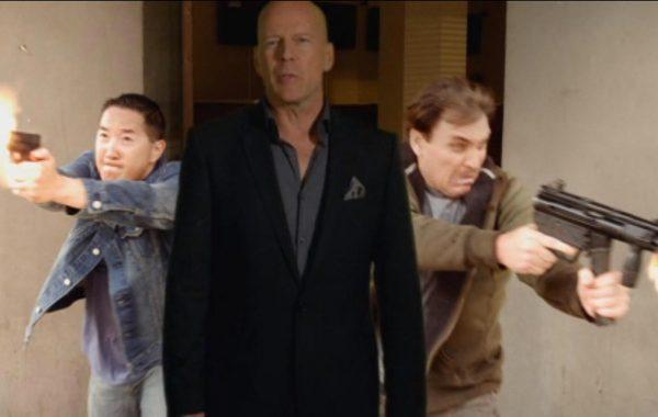 Grant Koo rushes through door, gun blazing, behind Bruce Willis