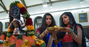Two students in traditional attire hold a gold plate in the Hall of Presidents during Diwali, the Hindu festival of lights.