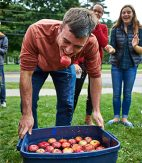 Student comes up with an apple in his mouth after bobbing for apples