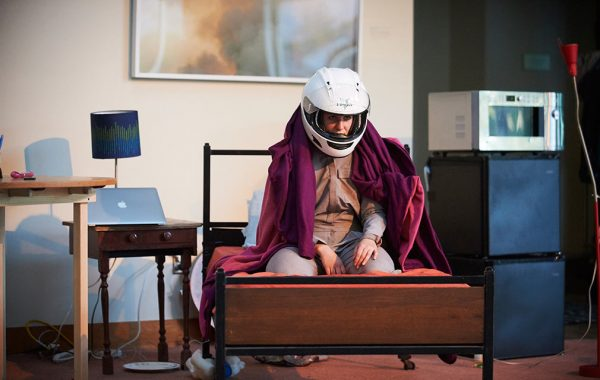 Dani Solomon '13 performing One Way Red, sitting on the end of a bed wearing a motorcycle helmet and draped in a blanket.