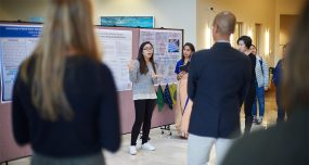 A Lampert Institute fellow presents a research poster to a gathered crowd.