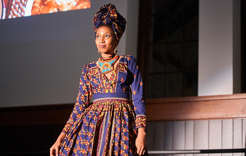 A female student in dressed in an outfit inspired by African fashion walks onto the catwalk